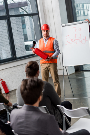 Photo pour handsome fireman in helmet giving talk on briefing while holding extinguisher near white board with fire safety lettering - image libre de droit