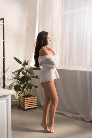 Foto de beautiful smiling woman in white shirt standing on tiptoe and looking away at home in morning - Imagen libre de derechos