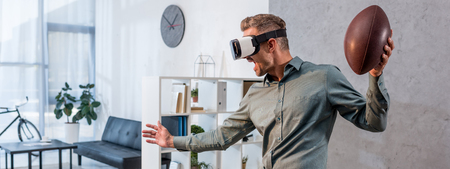 Foto de panoramic shot of excited businessman wearing virtual reality headset and holding american football - Imagen libre de derechos