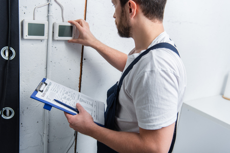 Foto de adult bearded electrician with clipboard checking electrical panel - Imagen libre de derechos