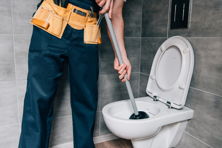 Foto de partial view of male plumber using plunger and cleaning toilet in bathroom - Imagen libre de derechos