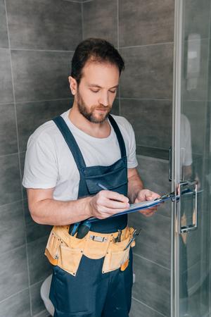 Foto de bearded male plumber making notes in clipboard while checking shower in bathroom - Imagen libre de derechos