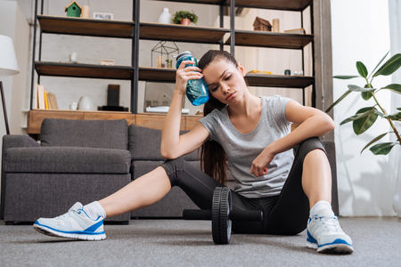 Photo pour tired sportswoman with sport bottle after training with ab wheel at home - image libre de droit