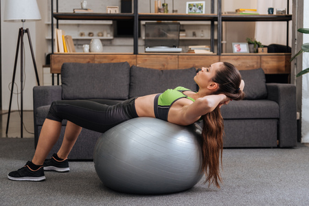 Photo pour focused sportswoman exercising with fitness ball at home - image libre de droit