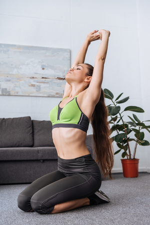 Photo pour young sportswoman stretching before workout at home - image libre de droit