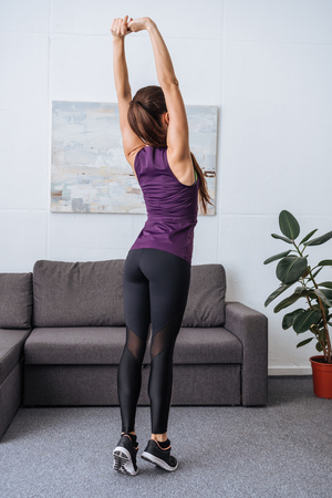 Photo pour back view of young sportswoman stretching before workout at home - image libre de droit