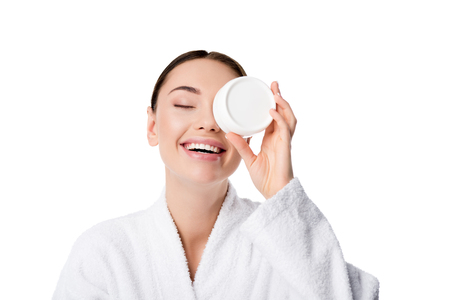 Photo pour cheerful woman in bathrobe holding moisturizing cream in front of face isolated on white - image libre de droit
