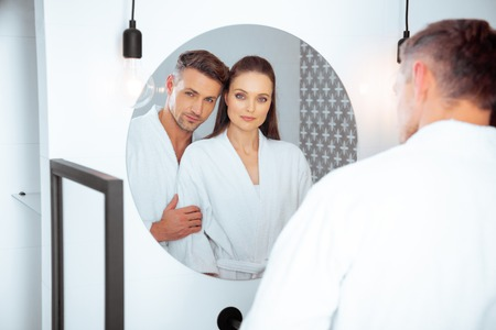 Photo pour handsome husband hugging attractive wife in bathroom while looking at mirror - image libre de droit