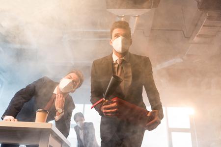 Foto de businessman in mask holding extinguisher near coworkers in office with smoke - Imagen libre de derechos