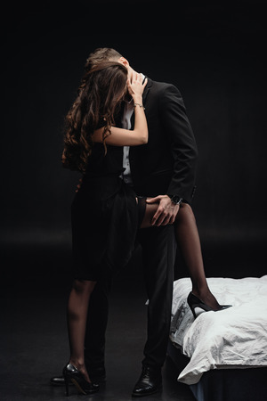 Foto de passionate young couple in formal wear kissing and embracing isolated on black - Imagen libre de derechos