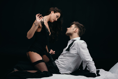 Foto de beautiful young woman in sexy lingerie undressing man isolated on black - Imagen libre de derechos