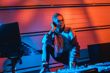 Photo for thoughtful dj woman in glasses touching dj mixer while listening music in headphones - Royalty Free Image