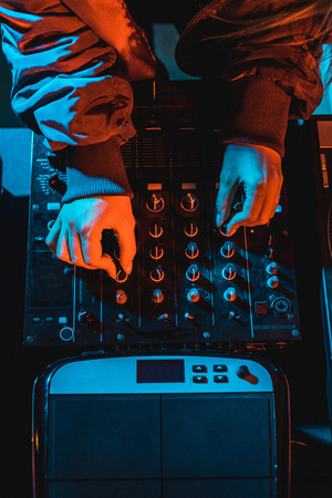 Photo for top view of dj woman touching dj mixer in nightclub - Royalty Free Image