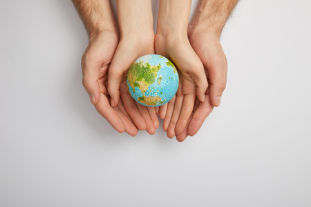Foto de top view of man and woman holding planet model on grey background, earth day concept - Imagen libre de derechos