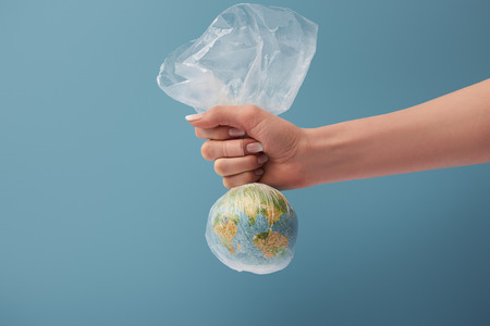Foto de cropped view of woman holding globe in plastic clear bag on blue background - Imagen libre de derechos