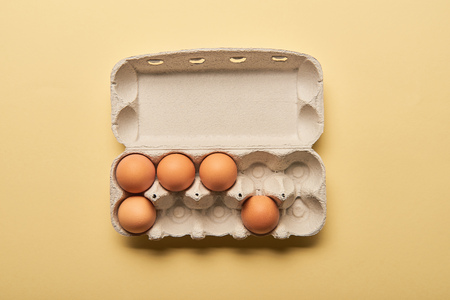 Foto de top view of brown organic eggs in cardboard box on yellow background - Imagen libre de derechos