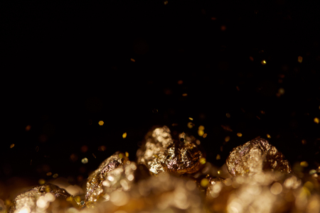 Photo pour selective focus of golden stones with sparkling lights isolated on black - image libre de droit