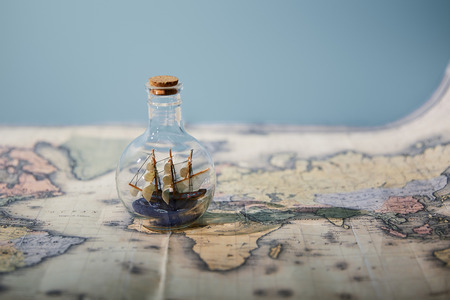Foto de Selective focus of toy ship in glass bottle and map with copy space isolated on blue - Imagen libre de derechos