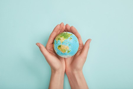 Photo pour top view of woman holding planet model on turquoise background, earth day concept - image libre de droit