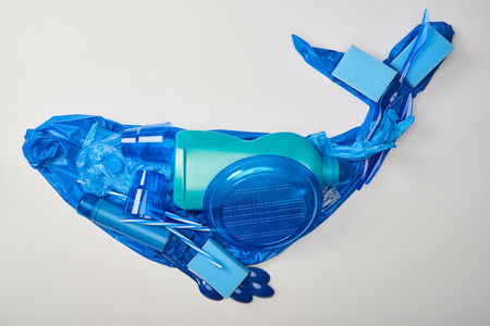 Foto de top view of whale made from disposable plastic tableware, bag, bottle, sponges and rubber gloves isolated on white - Imagen libre de derechos
