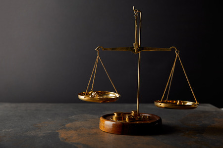 Photo pour golden stones on scales on marble table and dark background - image libre de droit