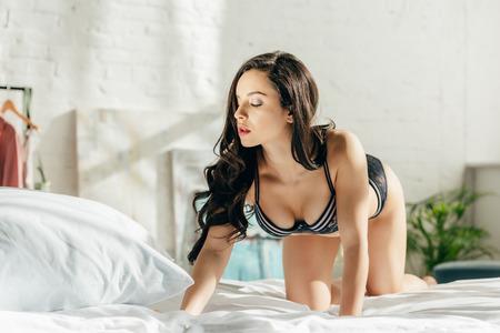 Foto de attractive brunette woman in lace lingerie on bed with white bedding - Imagen libre de derechos