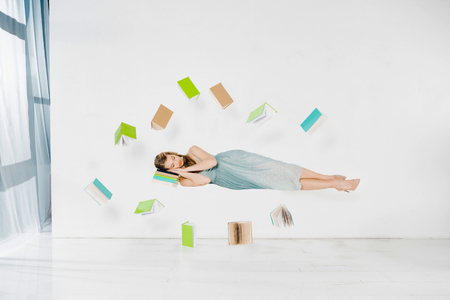Photo for floating girl in blue dress sleeping on book in air on white background - Royalty Free Image