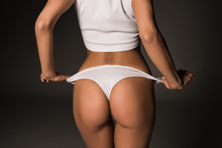 Photo pour Partial view of sexy girl taking off white panties on dark background - image libre de droit