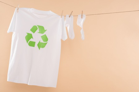 Photo pour t-shirt with recycling sign on clothesline near white socks isolated on beige, environmental saving concept - image libre de droit