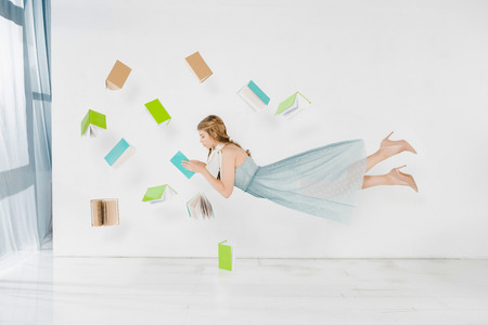 Photo for floating girl in blue dress reading book in air on white background - Royalty Free Image