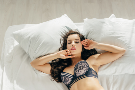 Foto de overhead view of beautiful brunette woman in bra lying on bed with closed eyes - Imagen libre de derechos