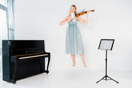 Photo for floating girl in blue dress playing violin and looking away on white background - Royalty Free Image