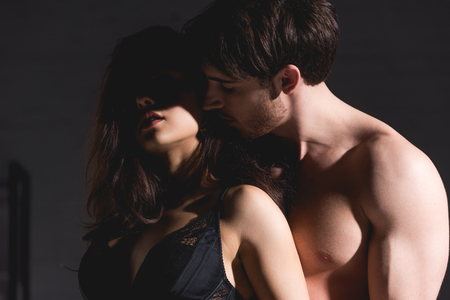 Photo pour woman in black lingerie and shirtless man standing and hugging on black background - image libre de droit