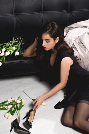 Photo for attractive brunette in black dress on floor with white tulips sitting near dark couch - Royalty Free Image