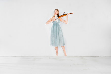 Photo for floating girl in blue dress playing violin on white background with copy space - Royalty Free Image