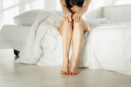 Foto de cropped view of sexy naked young woman sitting on bed - Imagen libre de derechos