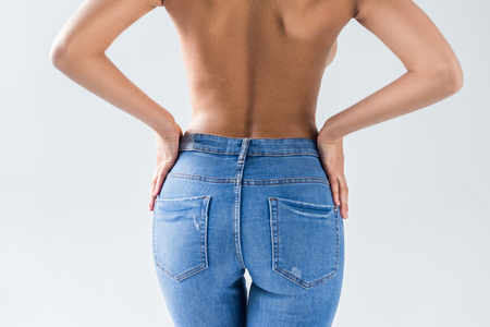 Photo pour Cropped view of nude sexy woman in jeans on grey background - image libre de droit