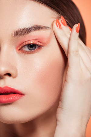Foto de beautiful stylish young woman with glitter makeup looking at camera isolated on coral - Imagen libre de derechos