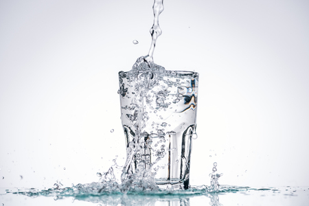 Foto de water pouring in full glass on white background with backlit and splashes - Imagen libre de derechos