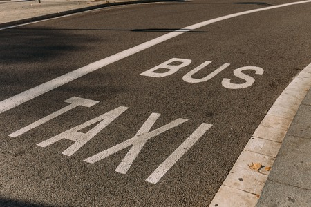 Photo for asphalt roadway with white markings, bus and taxi inscriptions, barcelona, spain - Royalty Free Image
