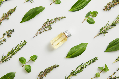 Foto de Flat lay with essential oil and fresh herbs on grey background - Imagen libre de derechos