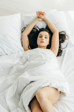 Foto de overhead view of attractive brunette woman wrapped in blanket lying on bed - Imagen libre de derechos