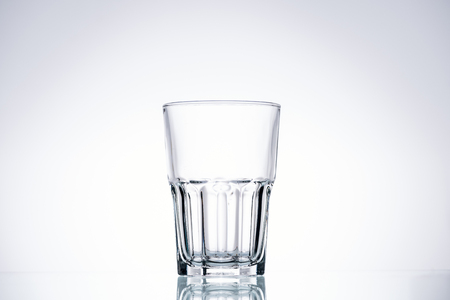 Foto de empty glass on white background with backlit and copy space - Imagen libre de derechos