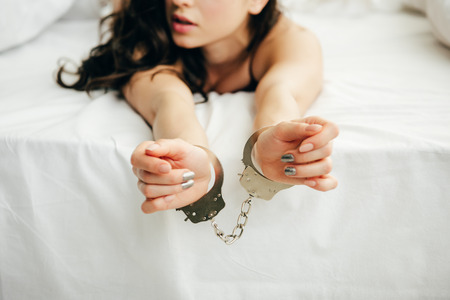 Photo for cropped view of young woman lying on bed with handcuffed hands - Royalty Free Image