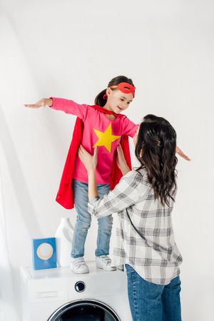 Foto de mother in grey shirt touching daughter in red homemade suit with star sign on washer in laundry room - Imagen libre de derechos