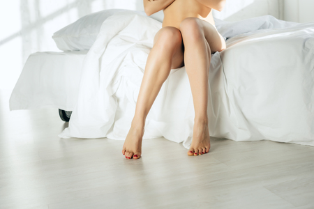 Foto de cropped view of sexy naked woman sitting on bed - Imagen libre de derechos