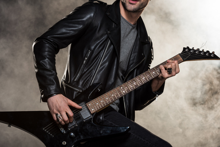 Photo for cropped view of rocker in leather jacket playing electric guitar on smoky background - Royalty Free Image
