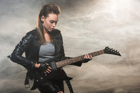 Photo for beautiful woman in leather jacket playing electric guitar on smoky background - Royalty Free Image