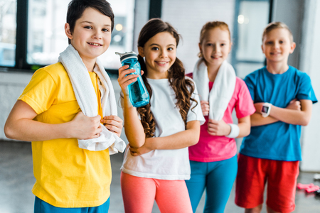 Photo for Group of kids with towels posing after training together - Royalty Free Image