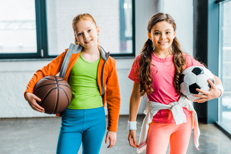 Photo pour Smiling children in sportswear holding balls in gym - image libre de droit